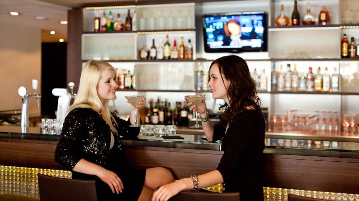 Guests enjoy drinks at the Marriott Frankfurt Hotel bar, by the light of Philips LED Lighting