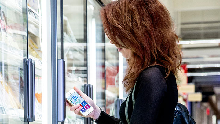 Woman using store app in frozen good section - increase shopping experience with indoor positioning