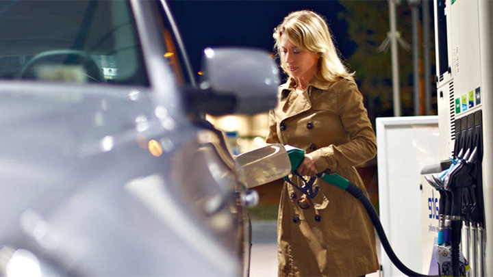 A woman fills her car's tank at a gas station under the bright lights of Philips canopy lighting.